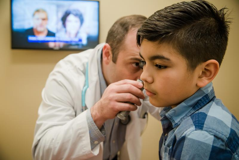 Doctor examines ears of a patient at urgent care.