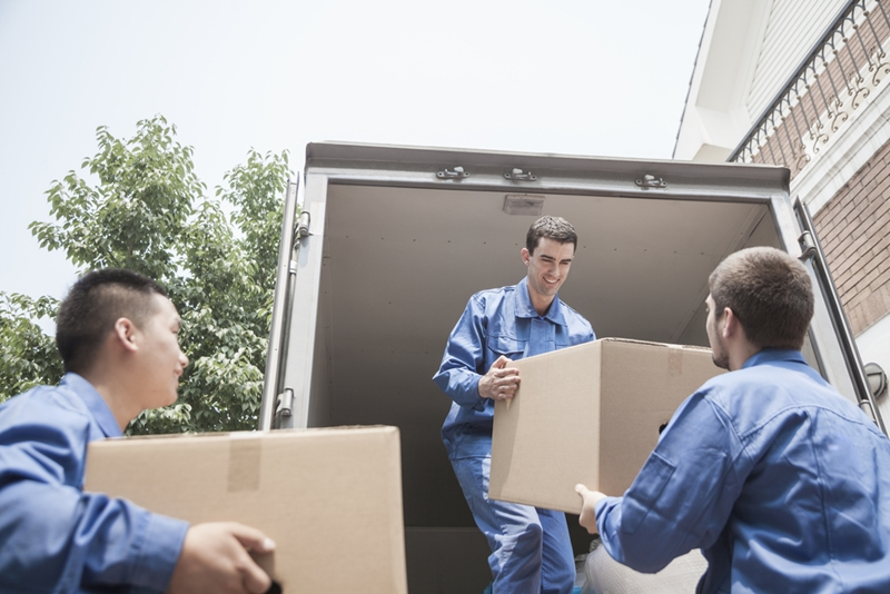 Three movers unloading a truck.