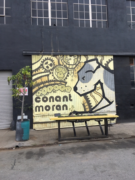 Victory Powder Coating & Sandblasting  Inc. - Los Angeles, CA. Straight on view of street art conant moran table and bar with chairs across from Nintendo controllers and Rubik's cube installations. At the corner of Broadway and 58th Street.